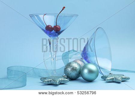 Festive Spirit Blue Martini Cocktai Glasses With Red Maraschino Cherries And Christmas Baubles On An