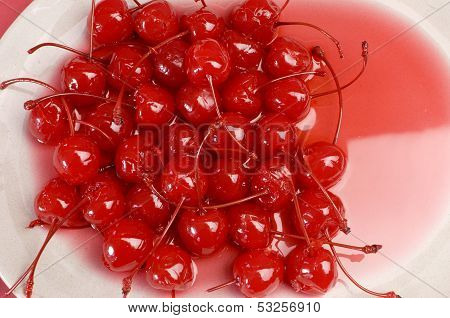 Festive Background Of Red Cocktail Maraschino Cherries With Stems - Close Up On A White Stone Plate