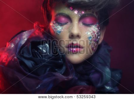 Close up portrait young woman with bright fantasy make up over red background