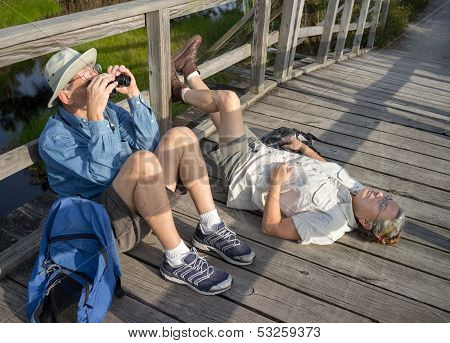 Seniors Birdwatching And Relaxing During Hike On Old Wooden Foot Bridge