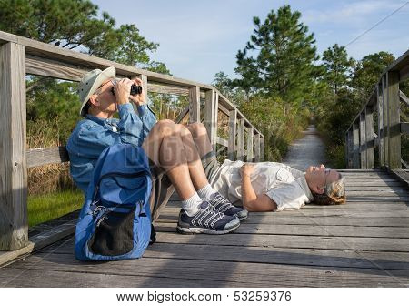 Seniors Birdwatching And Relaxing On Old Wooden Foot Bridge