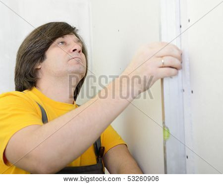 man with level make renovation indoor, plasterboard