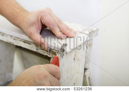 Man works with plasterboard, cut it with knife