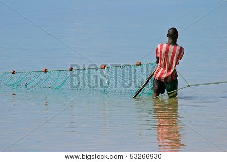 A mozambican fisherman pulling a fishing net from the water