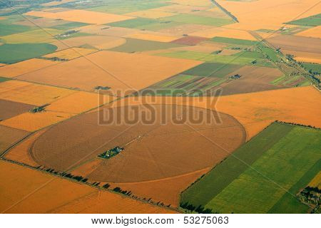 Aerial view of farmland with a mosaic of cultivated land and planted crops