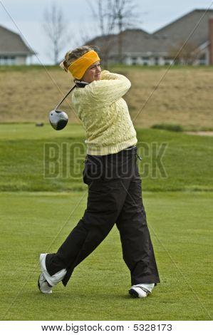 Female collegiate golfer swinging driver on tee box