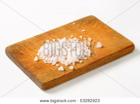 portion of crystal salt on a wooden cutting board