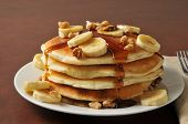 stock photo of walnut  - Banana nut pancakes with syrup in a stack - JPG