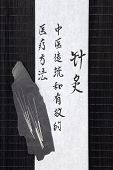 Acupuncture needles and mandarin script on rice paper over bamboo. Translation describes acupuncture