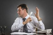 stock photo of disrespect  - Annoyed indifferent businessman having an uninteresting phone conversation while holding receiver facing the other hand palm in a talk - JPG