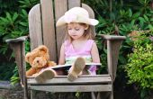 image of storytime  - Little girl pretending to read to her teddy bear - JPG