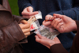 stock photo of crack addiction  - Drug dealer selling pillsmarijuana and cocaine to teens - JPG