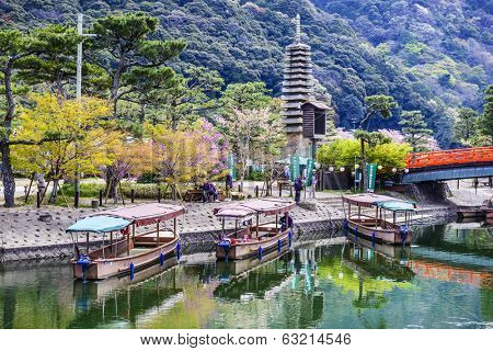 UJI, JAPAN - APRIL 12, 2014: Gondoliers prep boats for cruises on the Uji River in Kyoto Prefecture. The same boats are used for Cormorant fishing in the summer months.