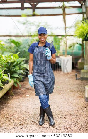 happy african nurser owner holding a shovel in greenhouse