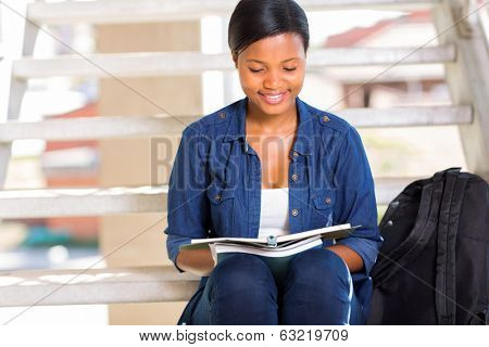smart african american university student reading a book outdoors