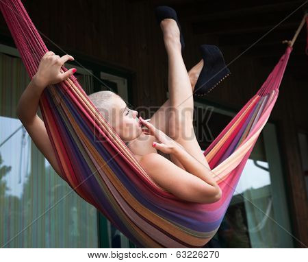 Nude Woman With Cigarette Resting In A Hammock
