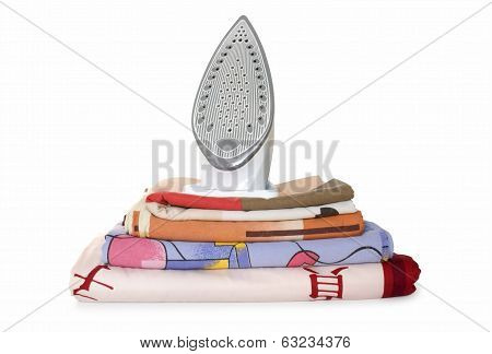 bedclothes in stack and iron isolated on white