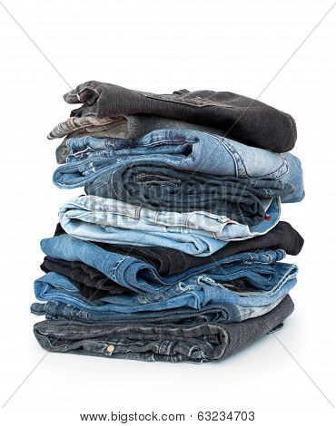 Stack of denim clothes on white background, jeans and jacket.