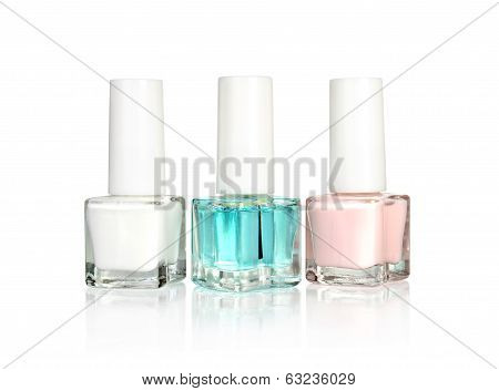 Nail polish bottles of various colors stacked isolated on white background