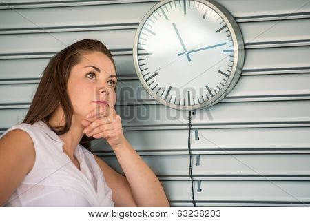 Business woman waiting by an analogue clock