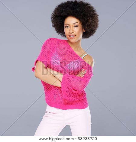 Sexy young African American woman with a frizzy afro hairstyle wearing a stylish pink blouse square format on grey