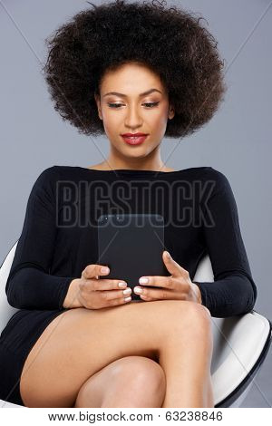 Beautiful African American woman reading her tablet as she sits in a modern armchair in an elegant black dress, close up view
