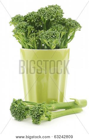 A small form of broccoli, called bimi, in a green ceramic mug on a white background