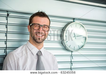 Happy business man posing with the analogue clock