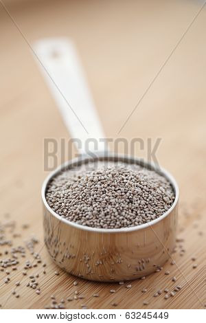 White Chia Seeds In A Measuring Cup On A Cutting Board