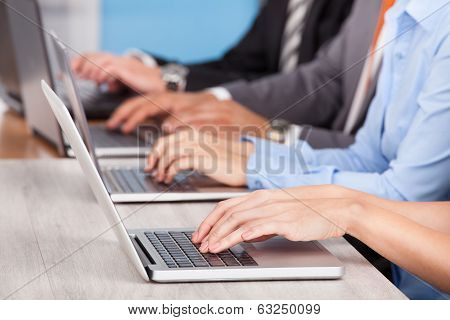 Close-up Of Businesspeople Using Laptop