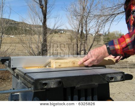 Sawing wood on a table saw.