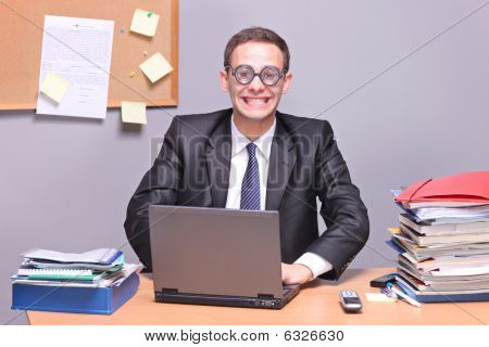 Nerdy businessman working on a laptop