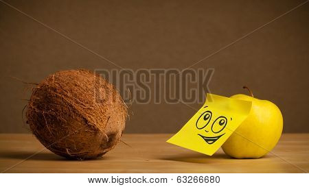 Apple with sticky post-it note reacting to coconut