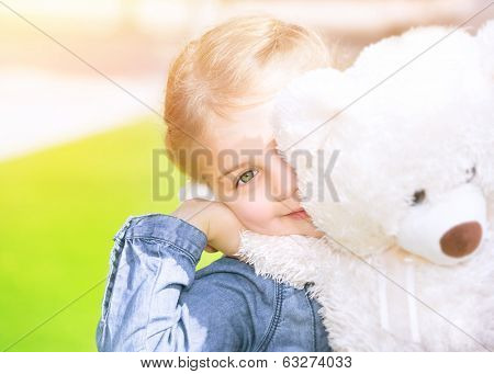 Cheerful little girl with soft bear toy playing outdoors, having fun on backyard in sunny day, summer holidays, happy childhood concept