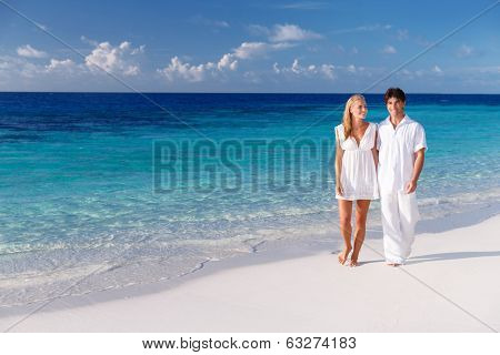 Happy couple walking along beautiful sandy beach, young family holding hands and enjoying honeymoon vacation on Maldives