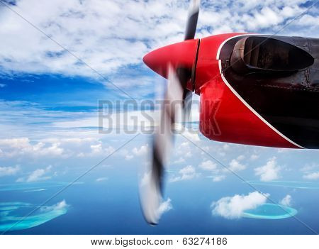 Summer traveling concept, small plane flying to the beach resort, scene destination, luxury aerial transport, tourism to exotic country