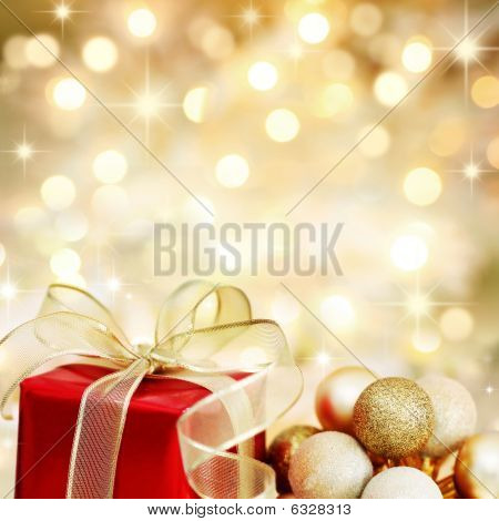 Christmas Gift And Baubles On Defocused Lights Background