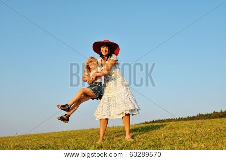 Cheerful mother rotating twisting making circle with her little daughter