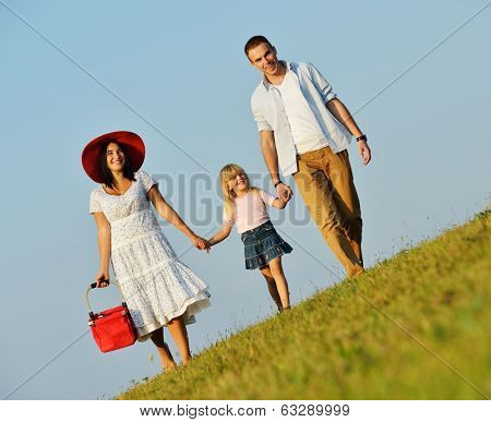 Happy family of three members on beautiful summer meadow enjoying and walking for picnic