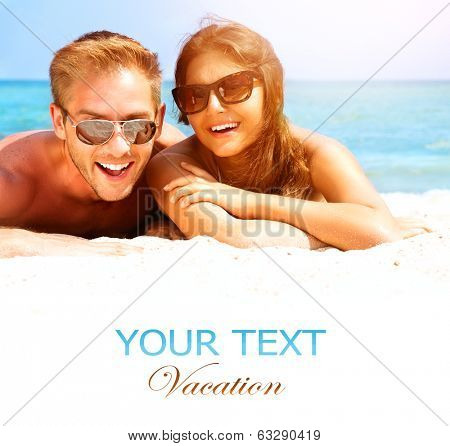 Happy Couple in Sunglasses having fun on the Beach. Summer Vacation. Laughing Family enjoying Nature over Sea Background. Attractive Man and Woman at the Beach. Sun tan