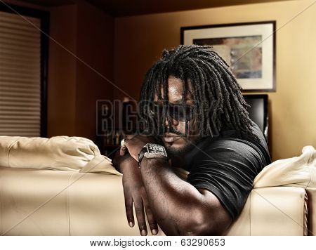 cool black man with dreads on leather couch.