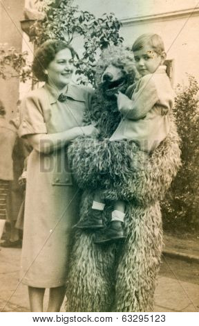 POLAND, CIRCA 1950's: Vintage photo of mother with little son posing with fake bear