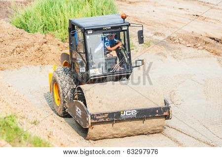 Road roller compressing sand to highway