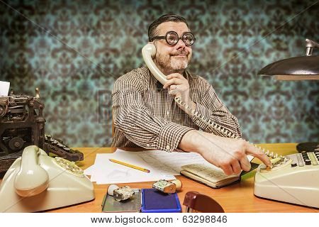 Employee with glasses talking on the phone in the office