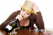 picture of bolero  - Young drunk woman by a table and with empty bottle - JPG