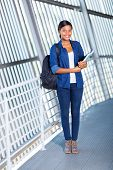 attractive female afro american student holding books