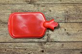 stock photo of hot-water-bag  - Hot water bottle or bag on wooden background - JPG