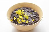 stock photo of phaseolus  - Closeup of bowl of black turtle beans garnished with yellow mustard flowers on white table - JPG