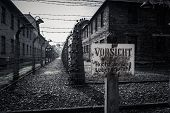 stock photo of nazi  - Electric fence and warning sign in former Nazi concentration camp Auschwitz I - JPG