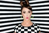 Attractive surprised young woman on stripes wallpaper background, beauty and fashion concept